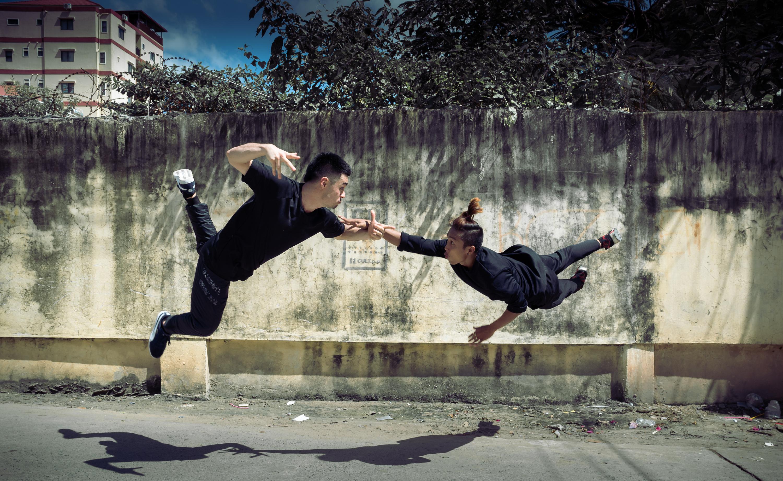 Two men dancing in the street.