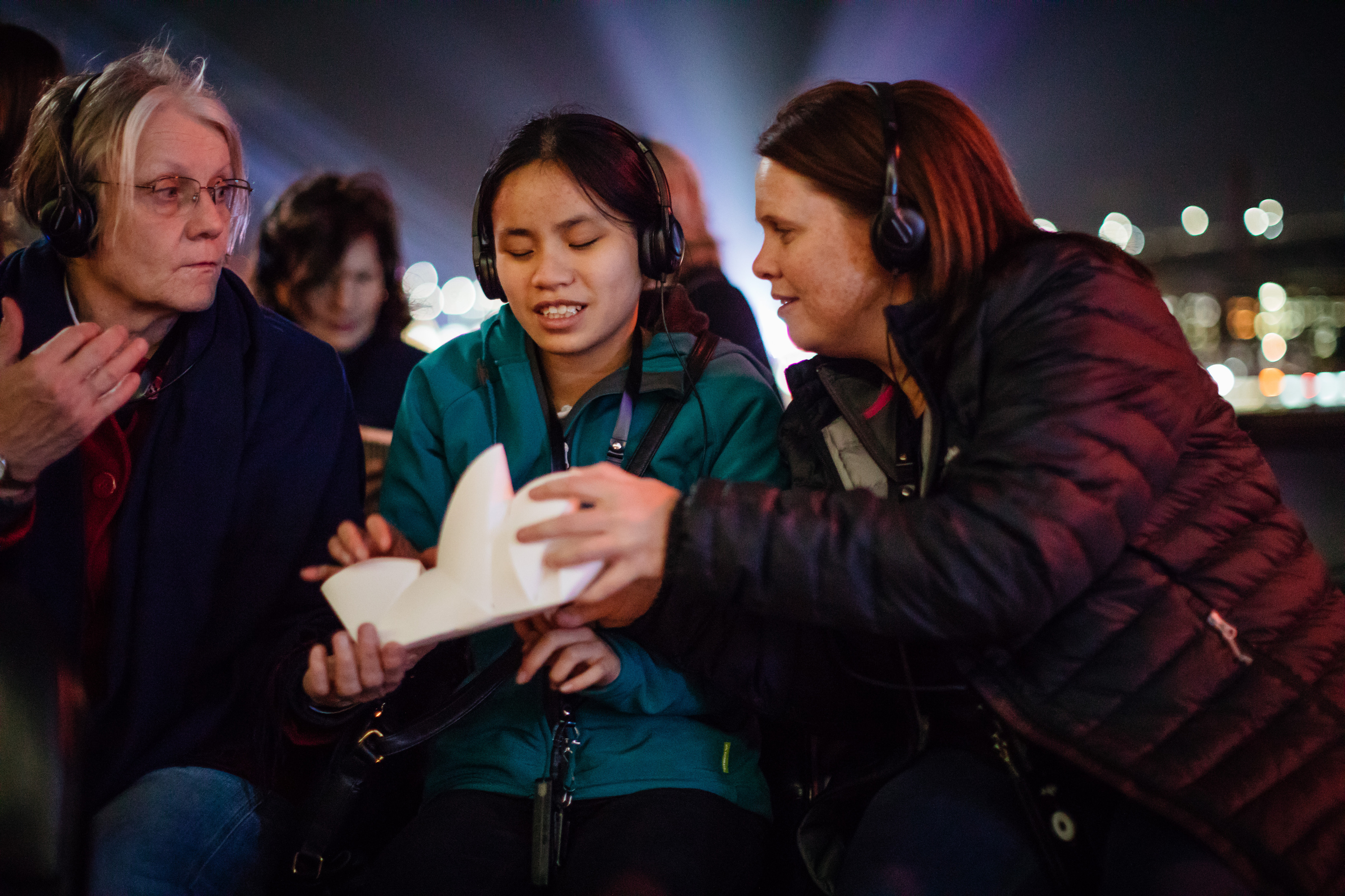 People holding a model of the Sydney Opera House on a live audio described tour during Vivid Sydney
