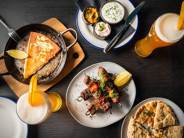 A spread of Greek food including saganaki cheese