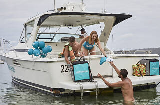 People hand a guy in the water a towel from a boat.