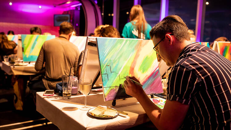 People painting on canvas and drinking wine.