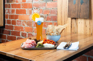 A cheese and cured meats board with a Blue Moon beer