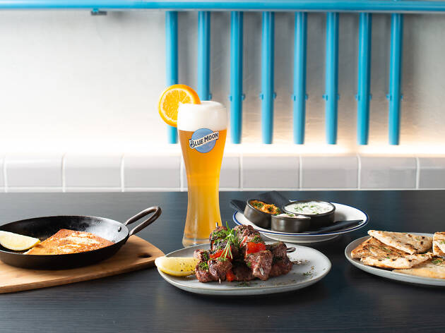 A spread of Greek food and a Blue Moon beer