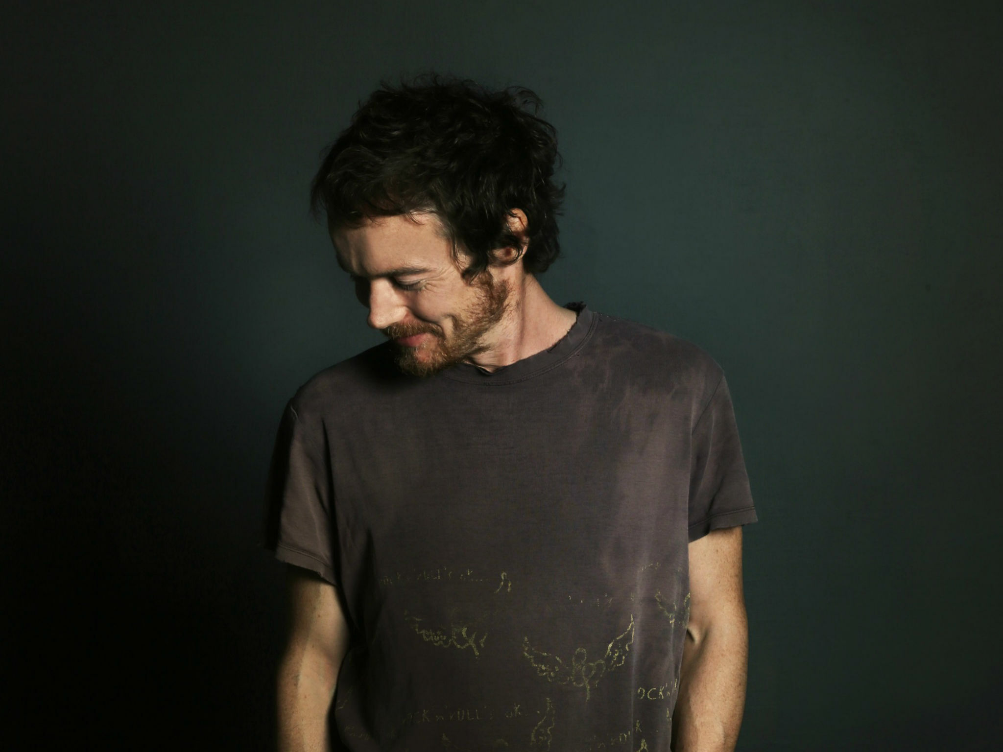 Musician Damien Rice looking down, to the right