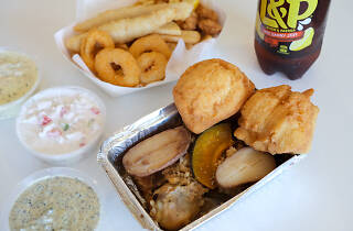 A box of meats, vegetables, stuffing and fried bread with sides