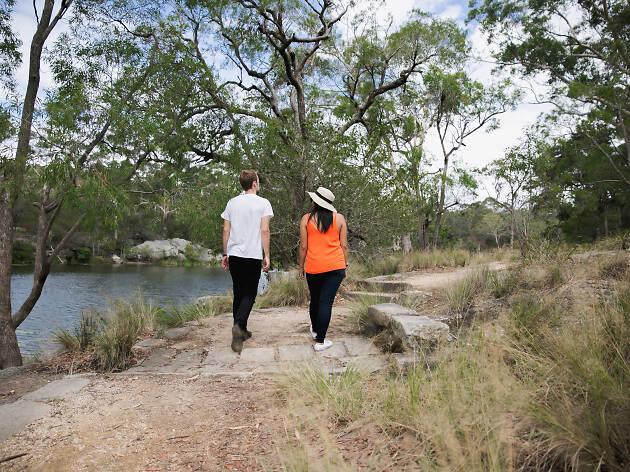 A couple walking around Lake Parramatta