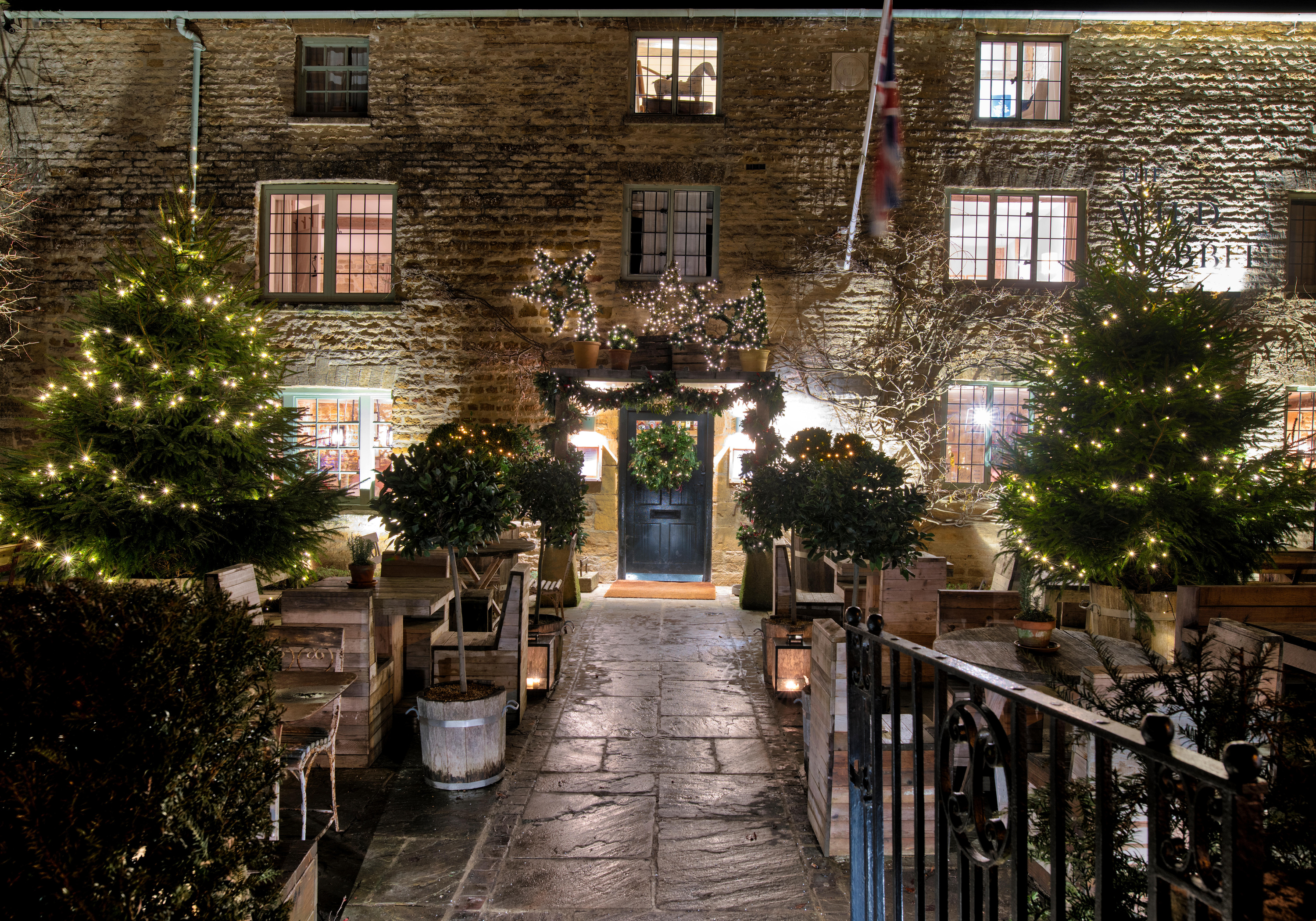 The Wild Rabbit pub with christmas trees and decorations at night in Kingham in December. Kingham, Cotswolds, Oxfordshire, England
