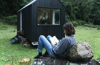 Person reading book outside tiny house in forrest at Unyoked