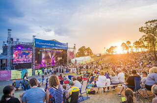 People sitting on a hill at sunset looking at a stage.