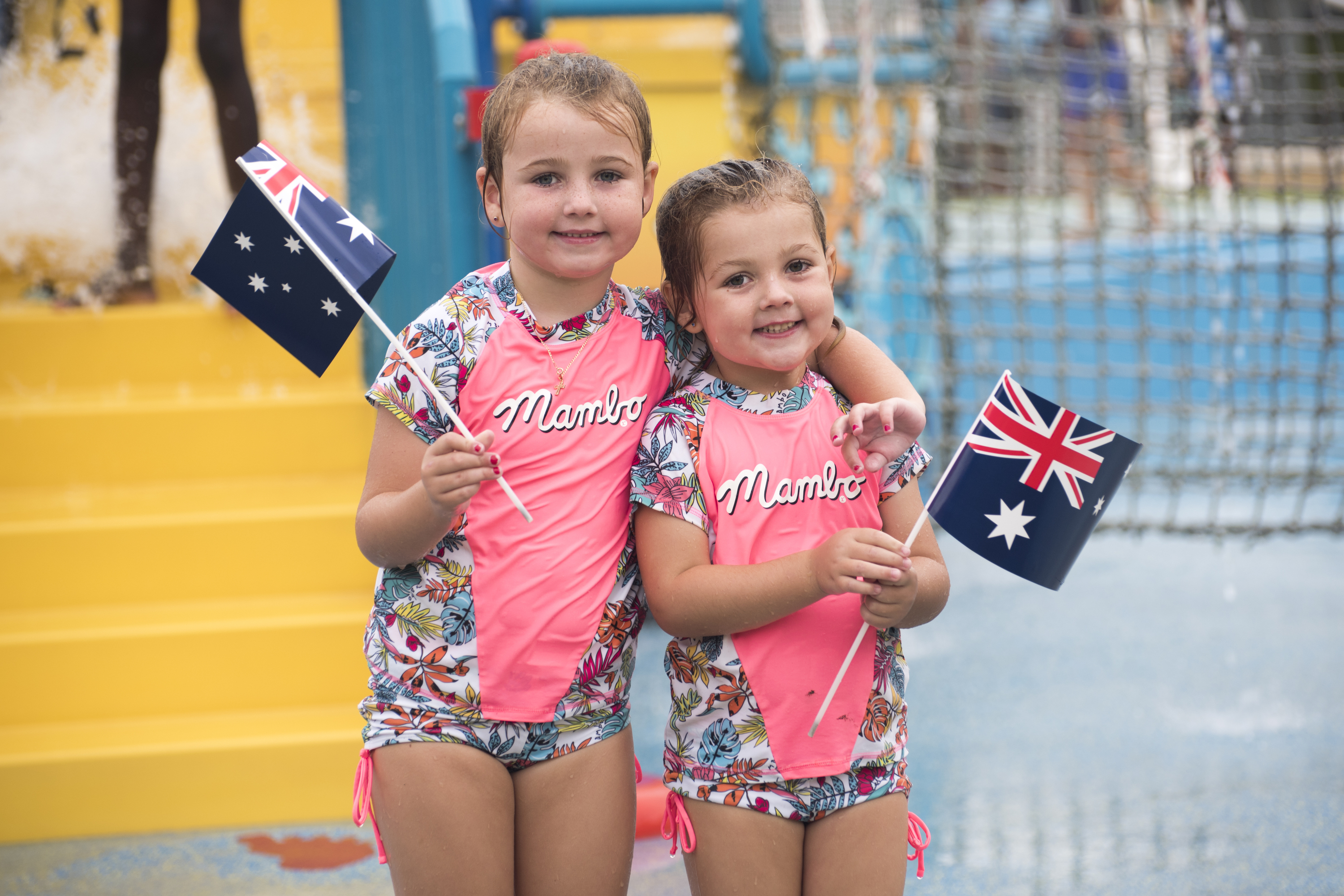 Kids in front of pool waving flags.