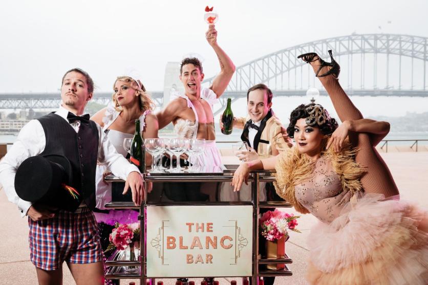 Actors posing in front of the Sydney Harbour Bridge.