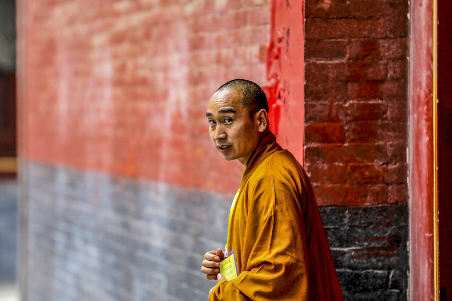 Monk standing near a red wall.