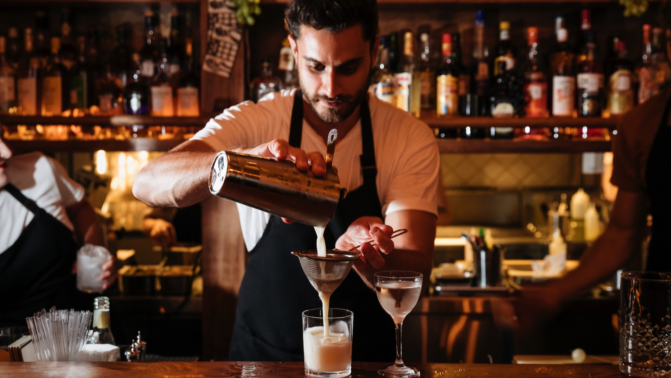 Person behind the bar making cocktails at Alberto's Lounge