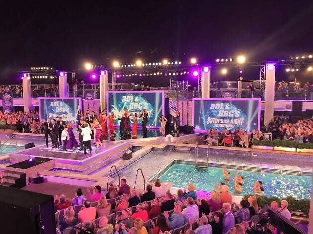 People watching game show at a pool.