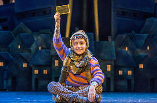 Actor playing Charlie bucket holds golden ticket on stage.