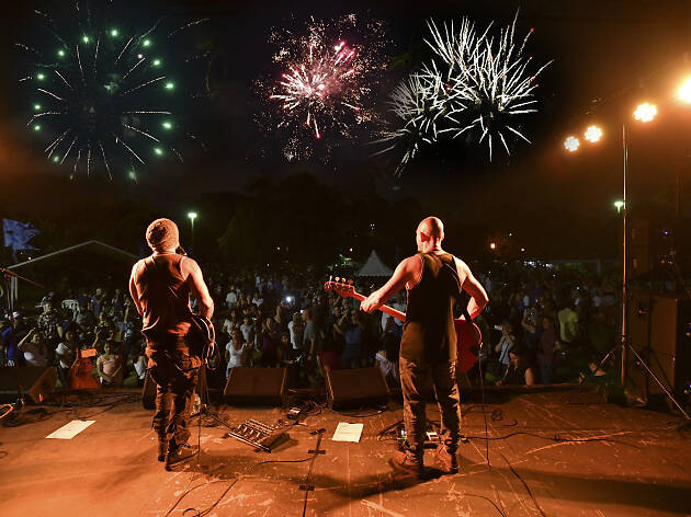 Band plays on stage to crowd and fireworks.