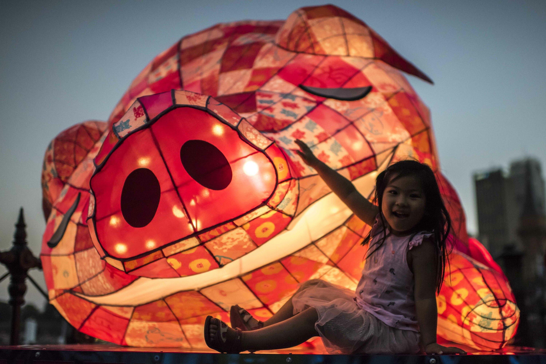 Kid sitting next to a pig lantern.