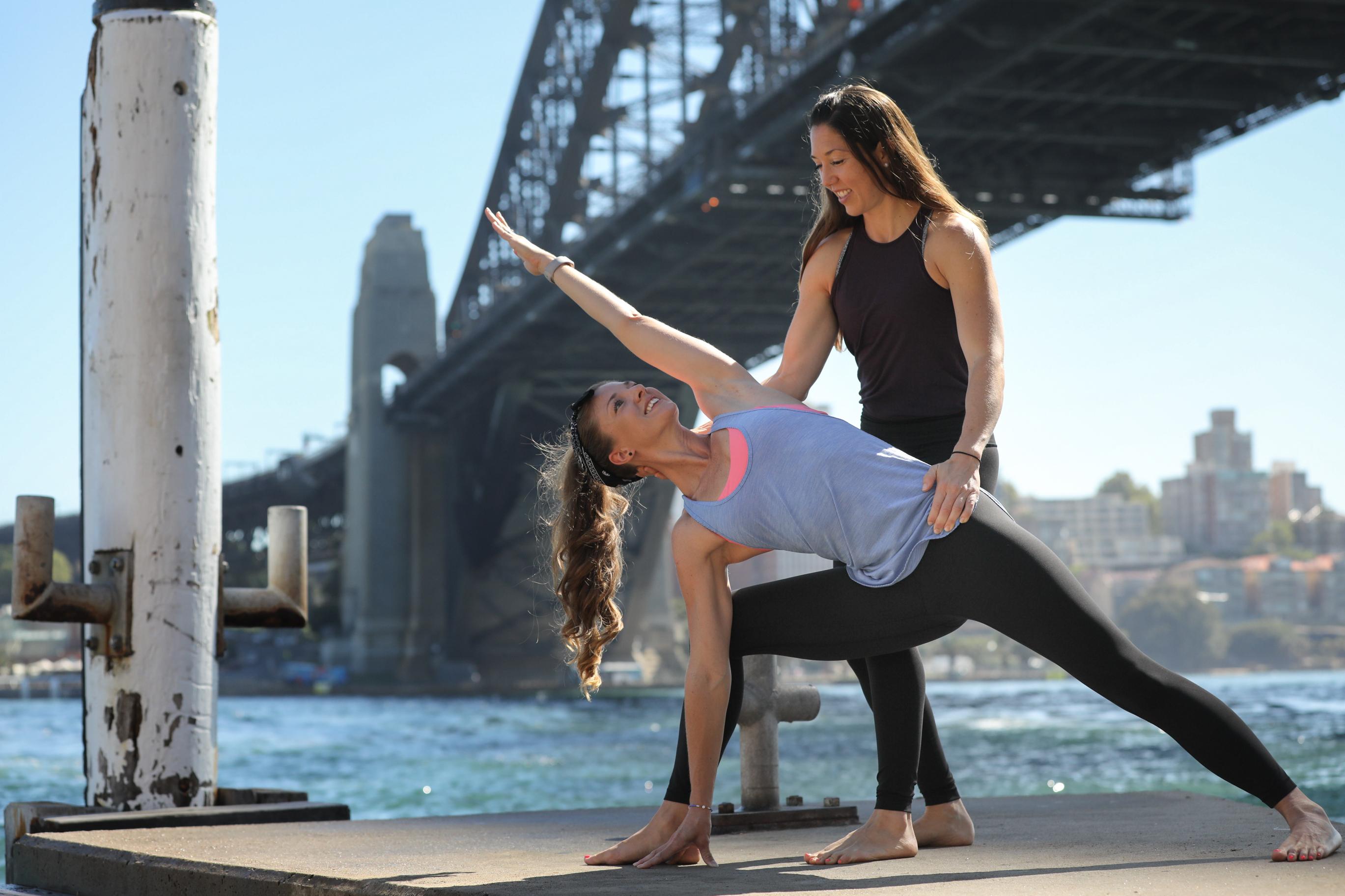 People doing yoga by the Sydney Harbour Bridge.