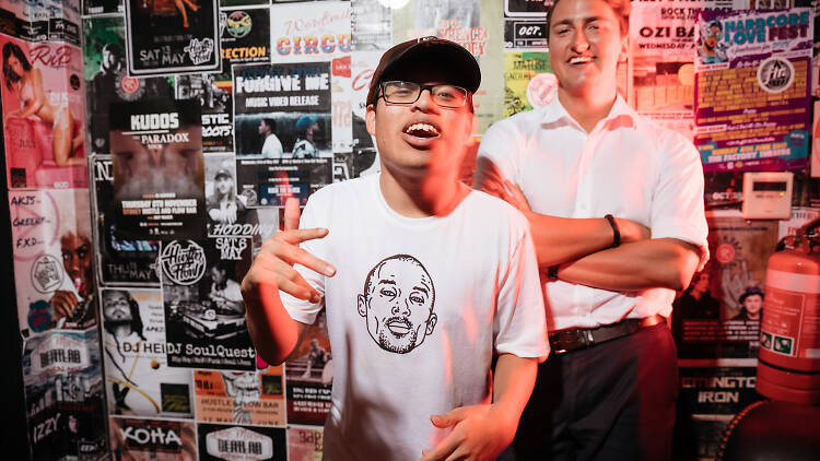 Gig Buddy Will rapping and volunteer David standing with arms crossed in front of music posters at Hustle and Flow