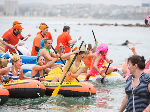 People in fancy dress paddling in the water at the Manly Inflatable Boat Race.