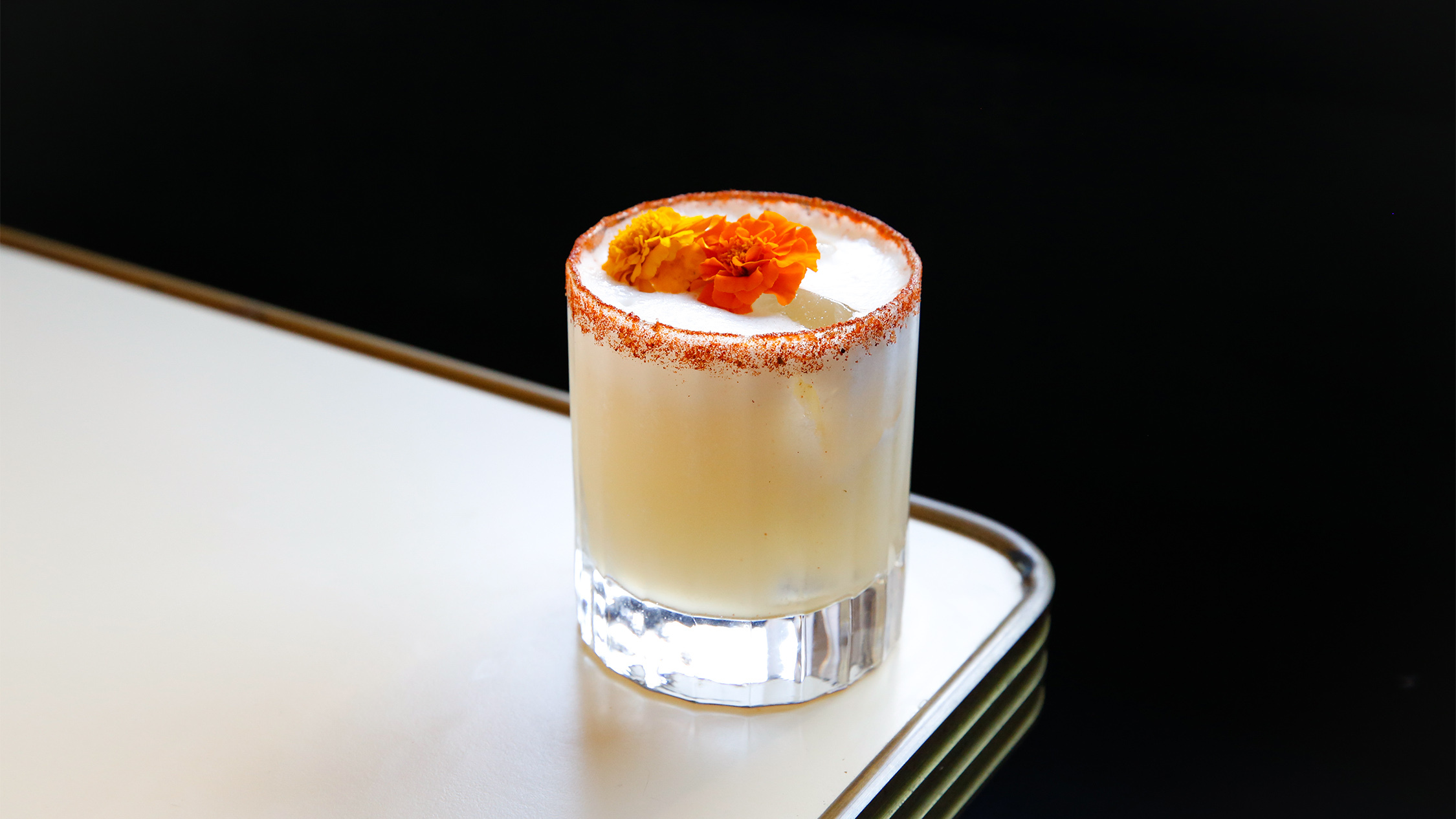 A while cocktail containing orange flowers on top sitting on the