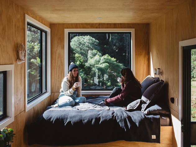 People sitting in a bed inside a cabin drinking coffee Unyoked