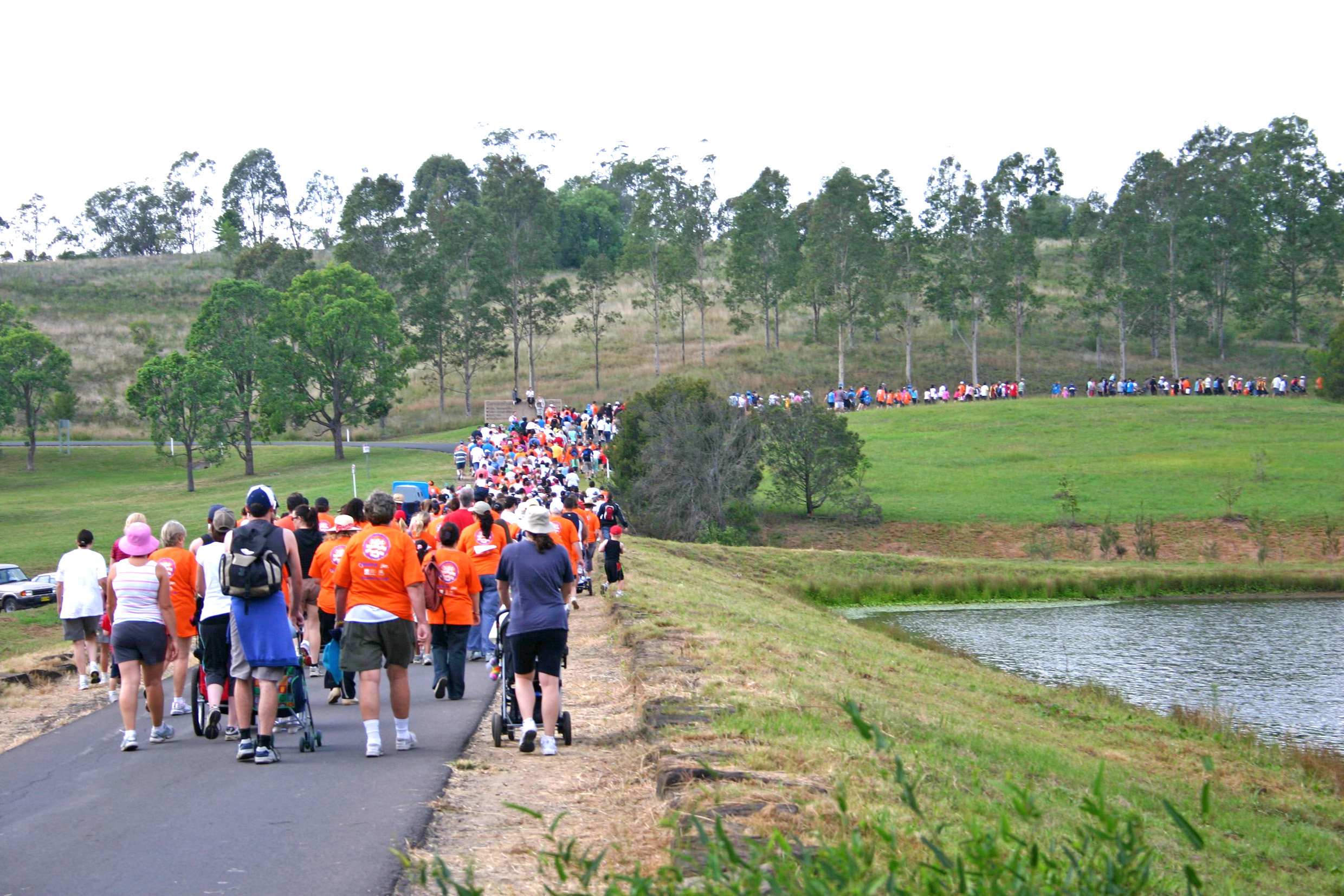 People walking past a lake on the Campbelltown City Challenge Walk.