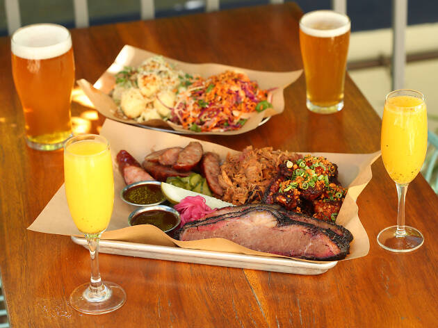 A plate of barbecued meats, sides, beers and Mimosas