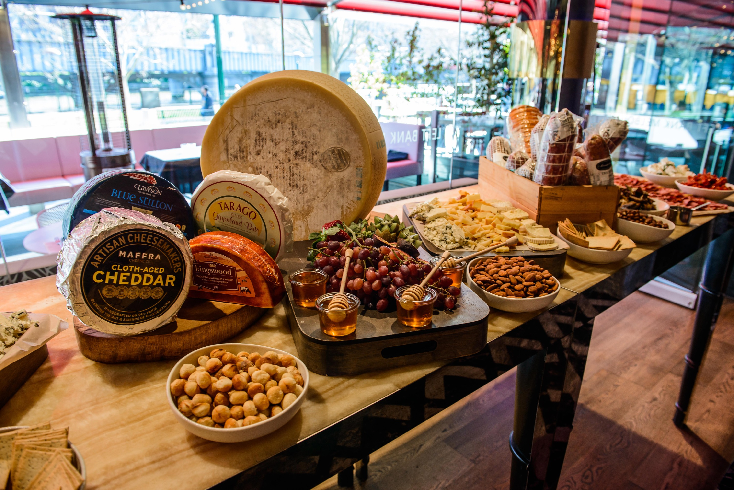 A buffet table with cheese, fruits and nuts