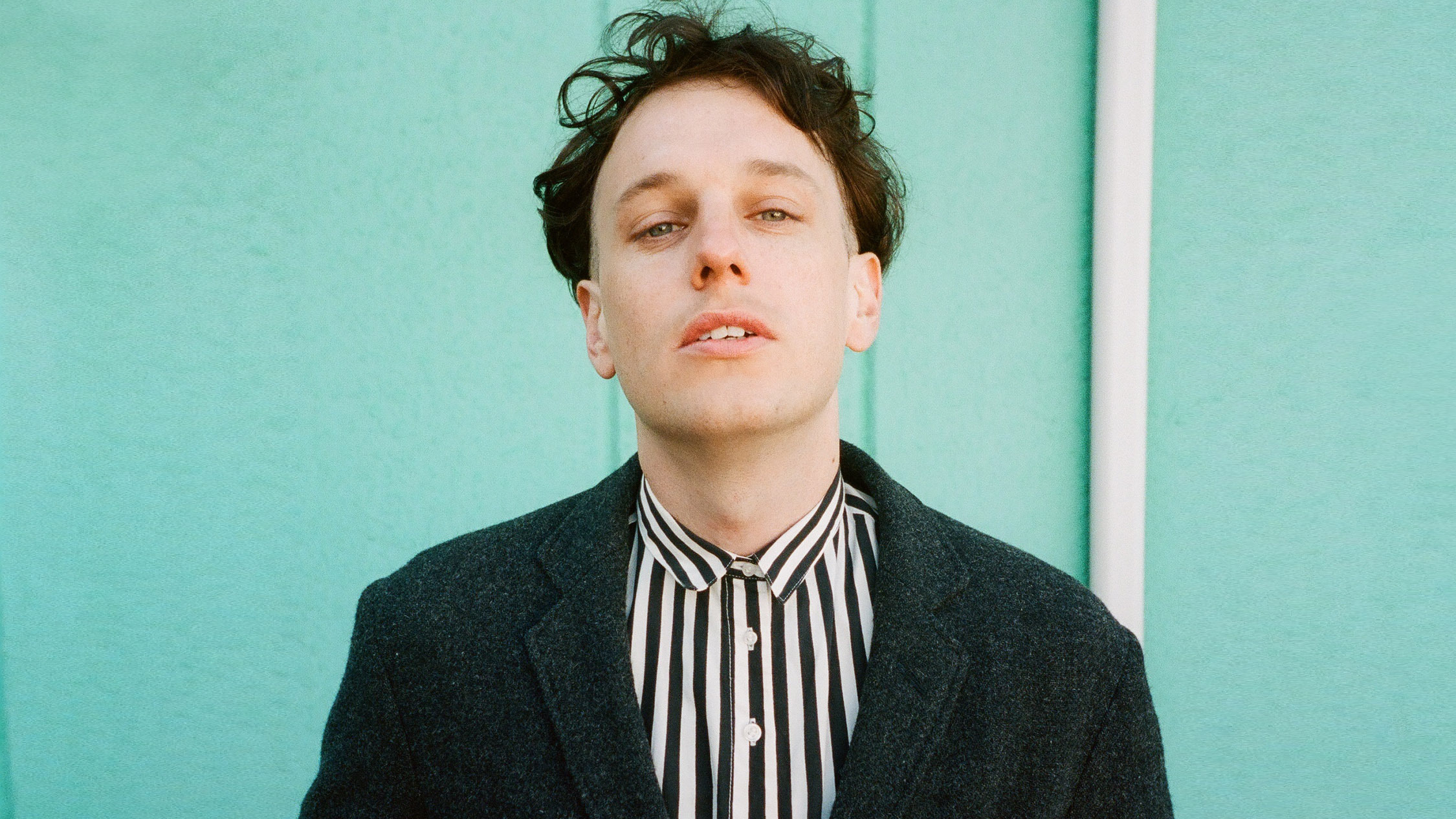 Band member from Methyl Ethel stands in front of a blue wall.