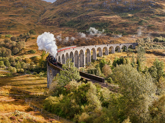 Aerial shot of viaduct arches with steam train