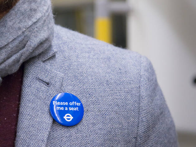 Close up of a man's Please Offer Me A Seat badge