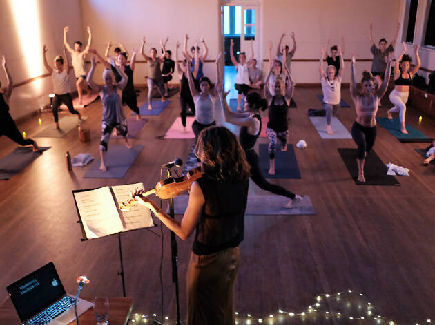 Violinist playing and people doing yoga in a church hall