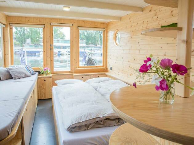light wooden walled houseboat with flowers and bedding