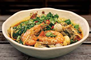 An individual bowl of hot pot with prawns