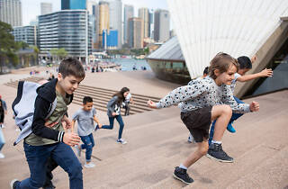 Kids running up the stairs of the Sydney Opera House on the Junior Adventure Tour.