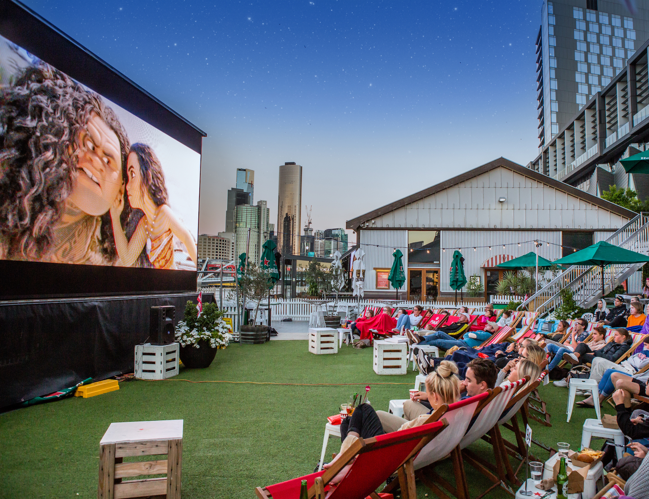 People seated on deckchairs to watch a movie on a big screen
