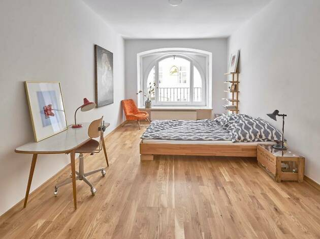 large bright bedroom with desk, art and arched window