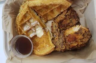 Waffles and fried chicken with a ramekin of syrup
