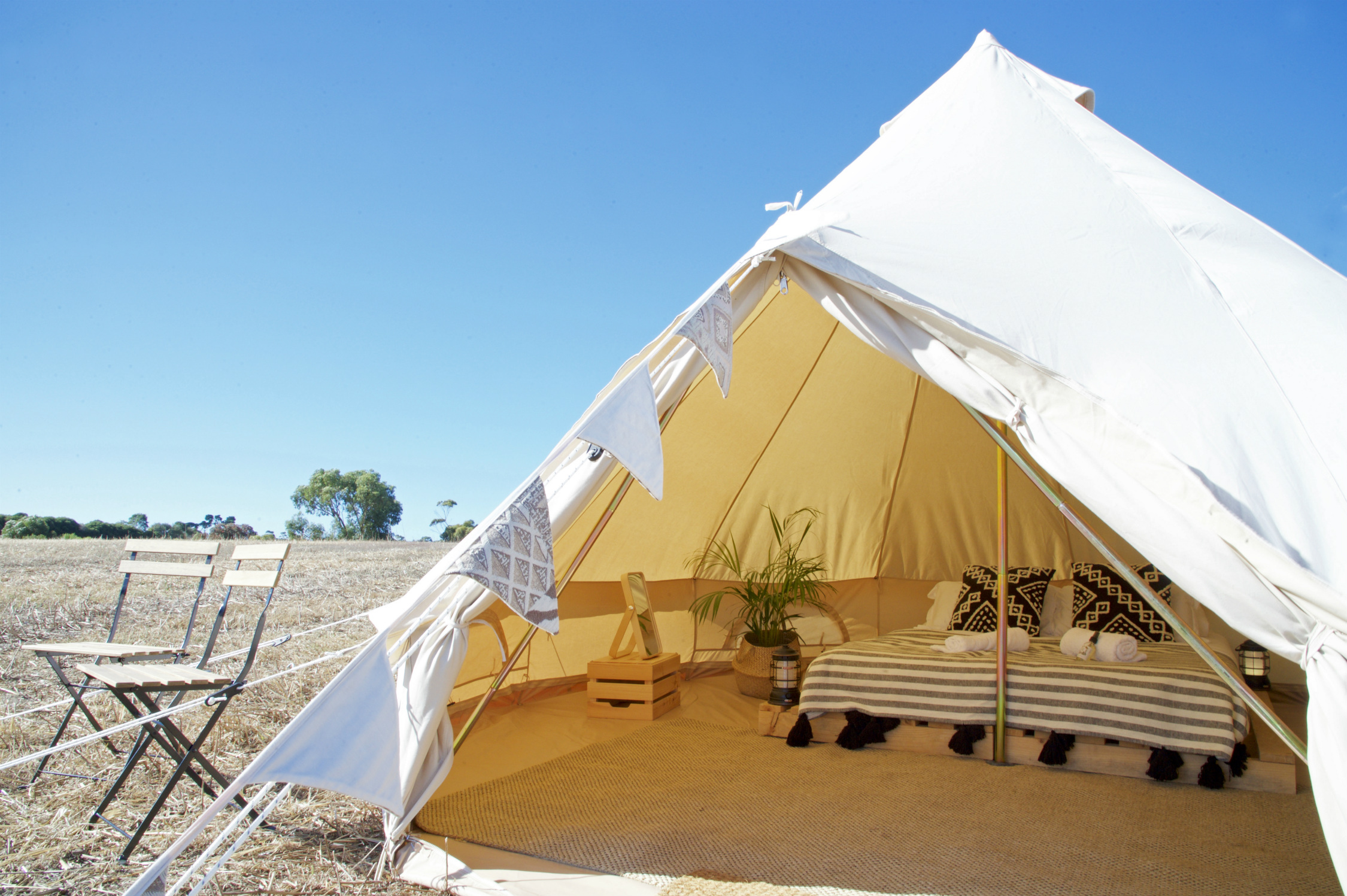 Canvas bell tent with entrance open, showing interior of tent