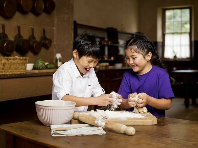 Two children preparing scone dough in the kitchen at Vaucluse House