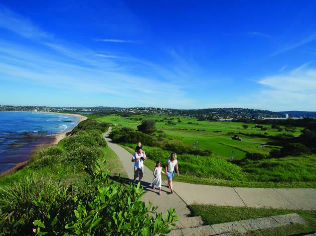 People walking along the Coast Walk pathway.