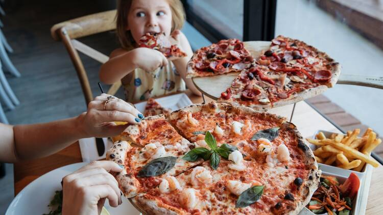 Child eating barbeque meat pizza at Bistro on the Greens