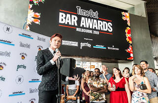Comedian Rhys Nicholson hosting the Time Out Bar Awards against a media wall backdrop