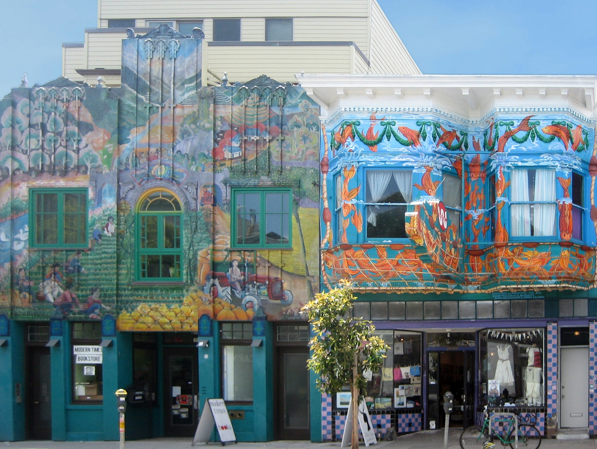Two colorful murals on the side of a city building