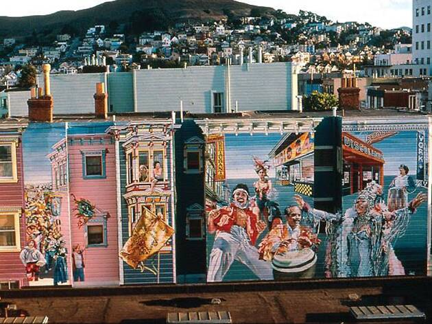 A colorful mural of Carnaval with a hill in the background