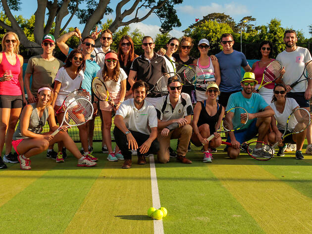 People posing on a tennis court.