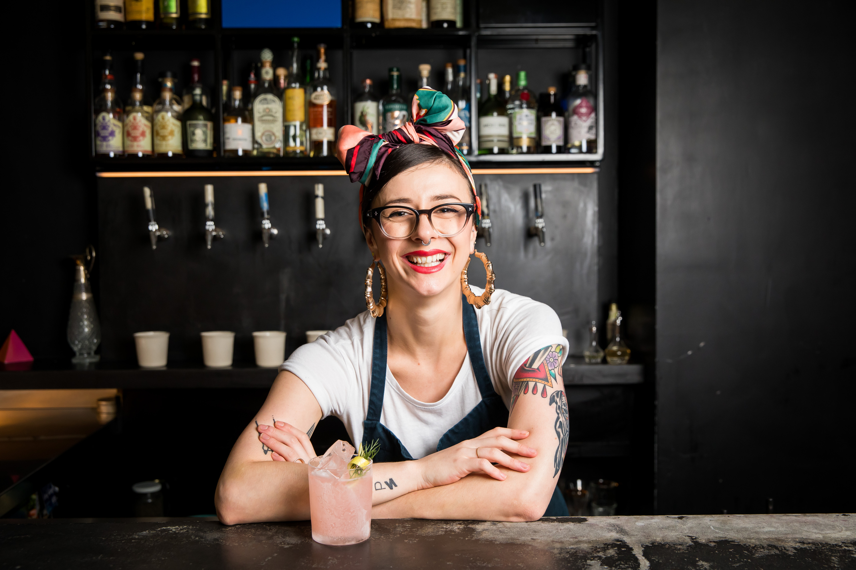 Person smiling behind bar with a cocktail