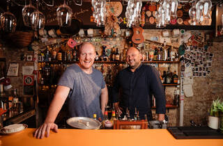 Two people standing behind bar