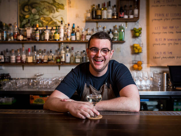 Man behind bar with cocktail in hand